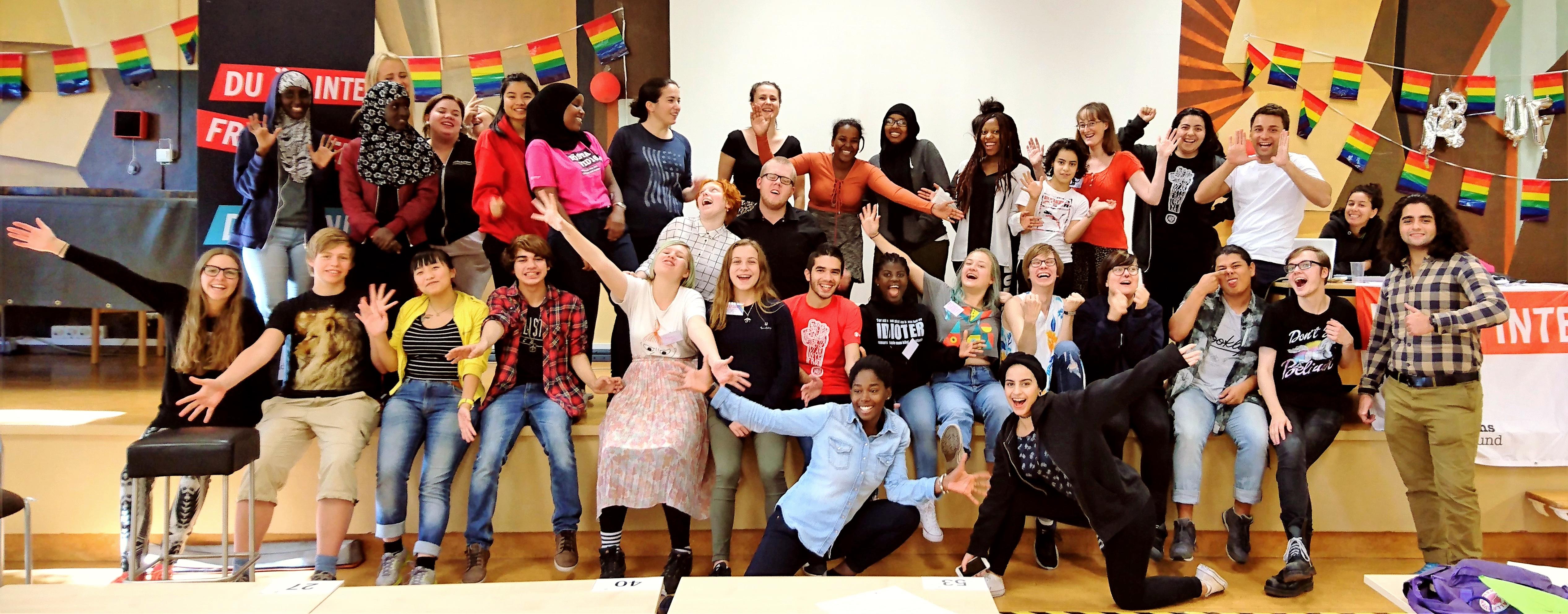 Ett fyrtiotal medlemmar i Rädda Barnens Ungdomsförbund som ser glada ut och sträcker ut armarna.