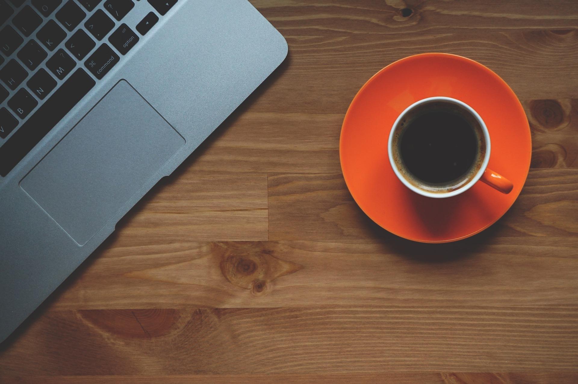 Bilden visar en kopp med kaffe bredvid en dator