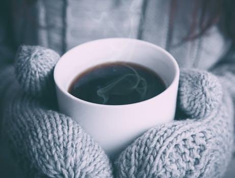 två vantklädda händer håller en vit mugg med brun dryck, troligen kaffe.